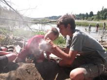 Youth learn to make friction fire with sticks in a Nature Studies program.